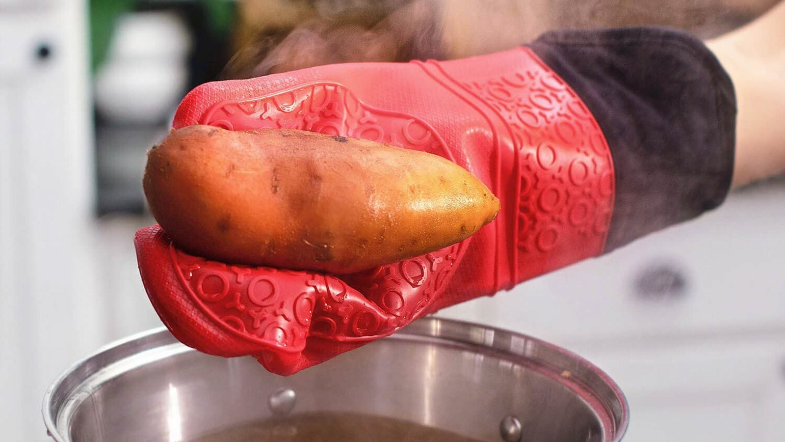 A red mitted hand lifting a yam out of a steaming pot.