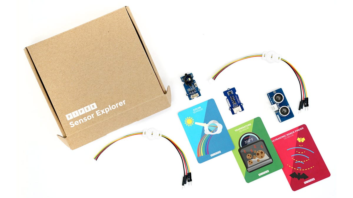 A Sensor explorer box, along with wiring, three sensors, and three trading cards.