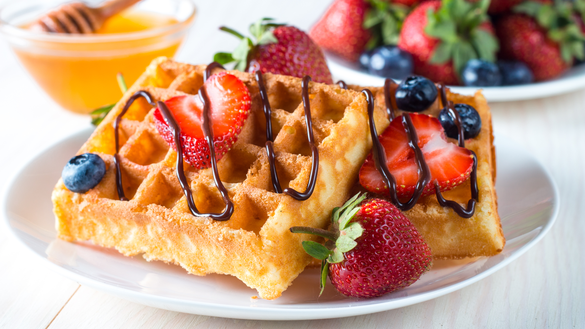 Two waffles on a plate, topped with strawberries, blueberries, and drizzled chocolate sauce.