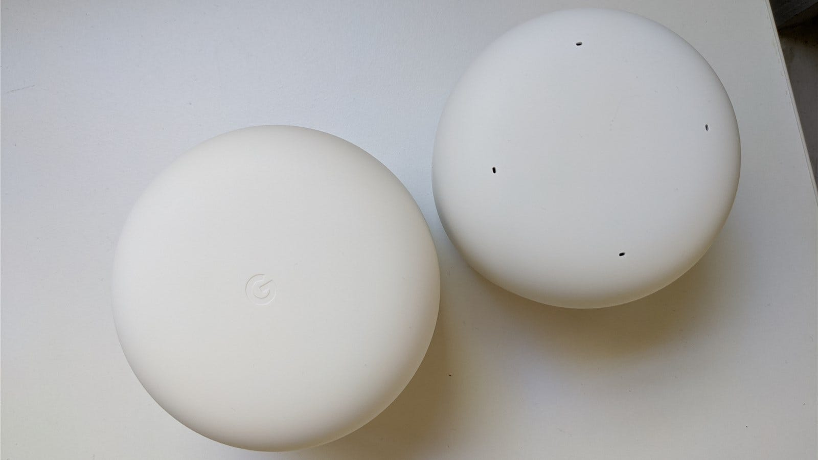 The tops of the Nest Wifi router and point