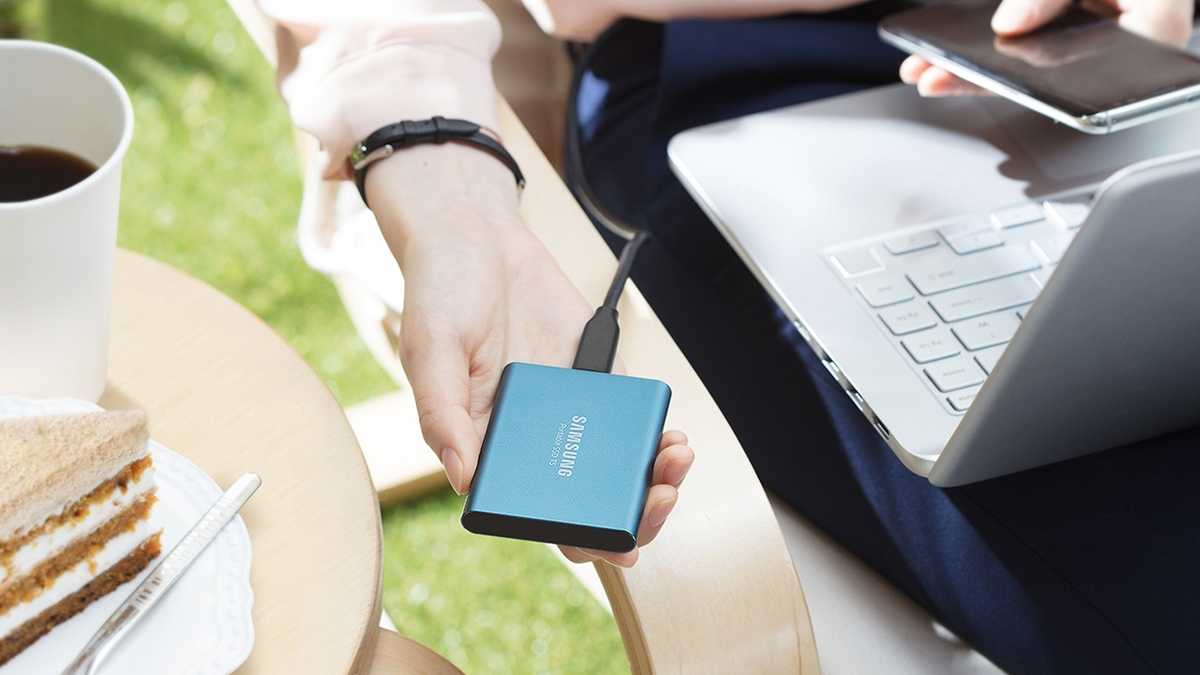 A hand holding a Samsung T5 portable SSD.