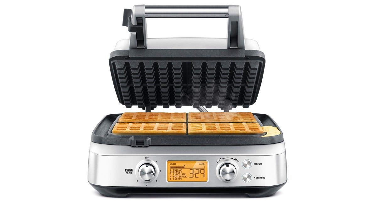 The Breville BWM640XL Smart Four-Slice Waffle Maker with it's lid open and four waffles on the tray.