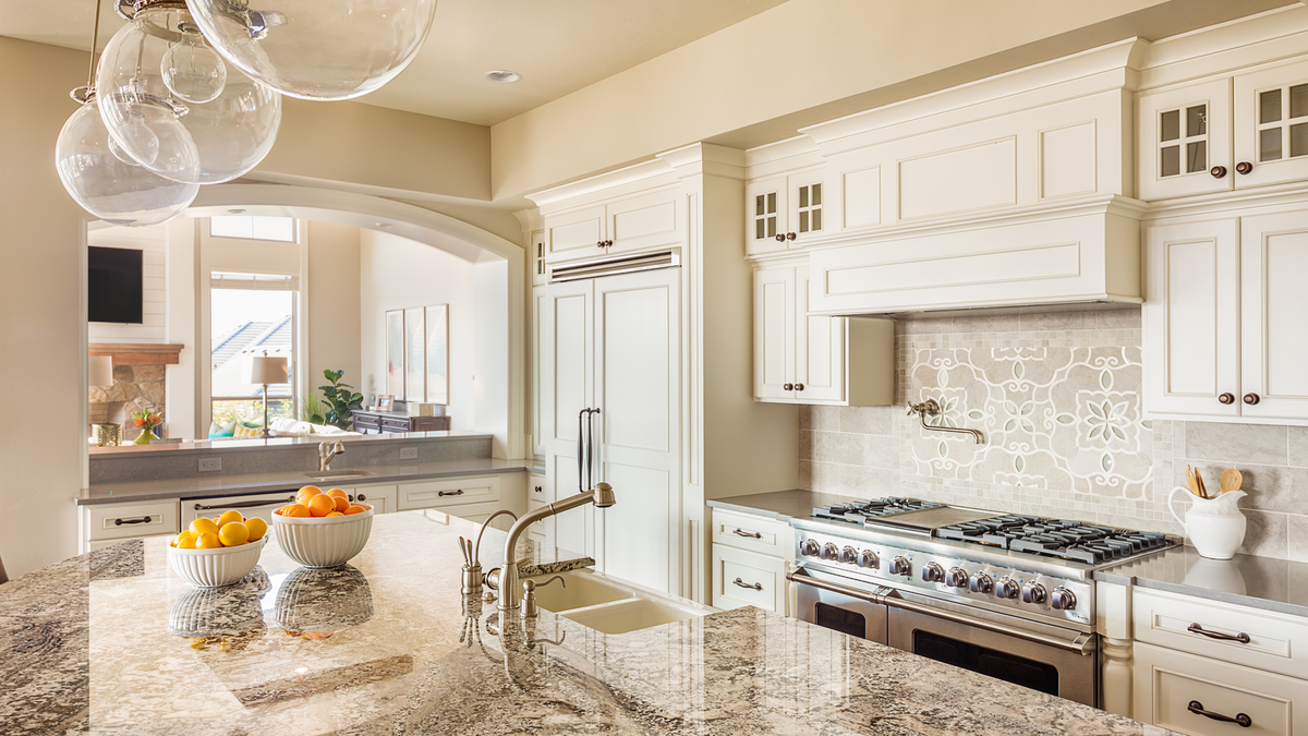A modern, white kitchen with a stainless steel range, two farm sinks, and marble-look granite countertops.