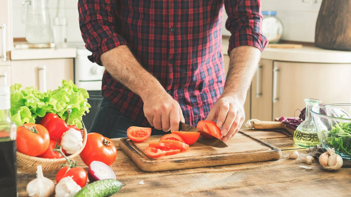A man slicing tomatoes on a cutting board with juice grooves in a kitchen.