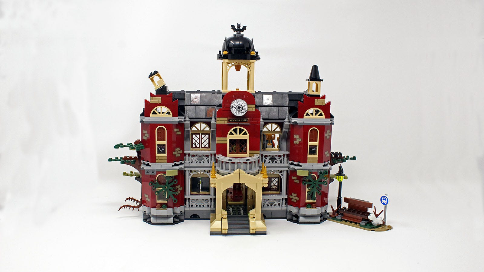 The front side of the Newbury High Lego set in regular mode, featuring a clock tower, plants, and an archway entrance.