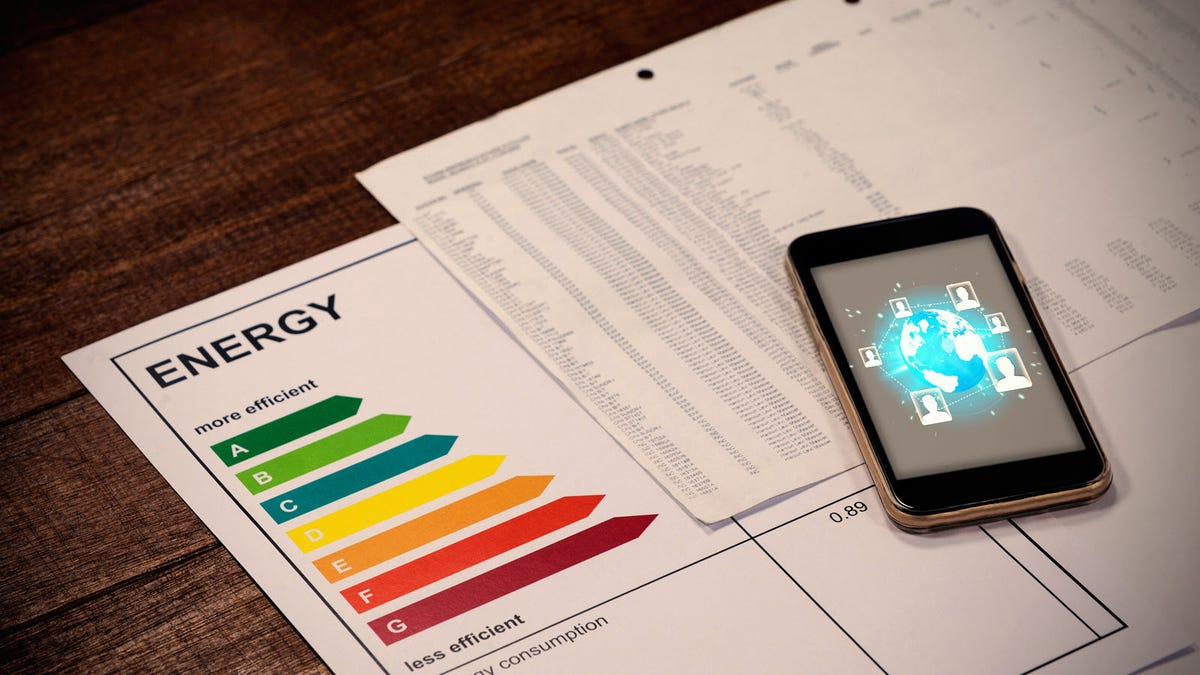Global technology wallpaper on a smartphone, lying on top of a printout of an energy efficiency graph.