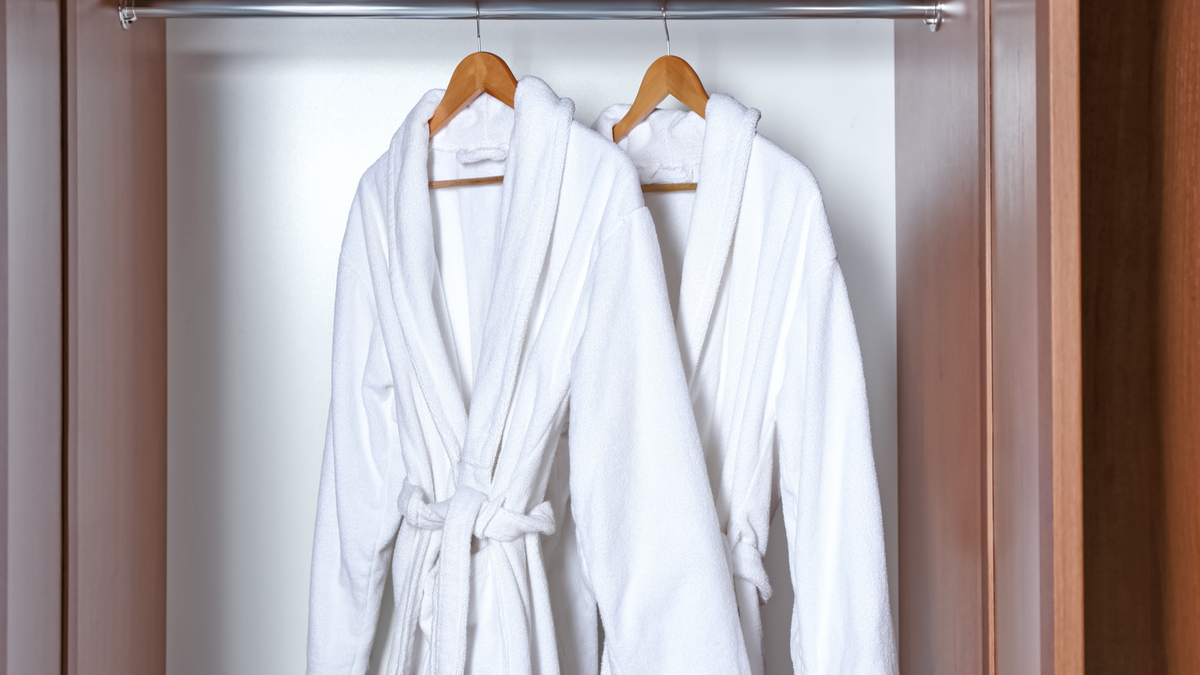 Two white bath robes hanging in a cabinet
