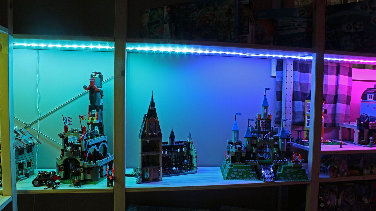 Three shelves of Lego bricks, one with green lights, one with purple, one with pink.