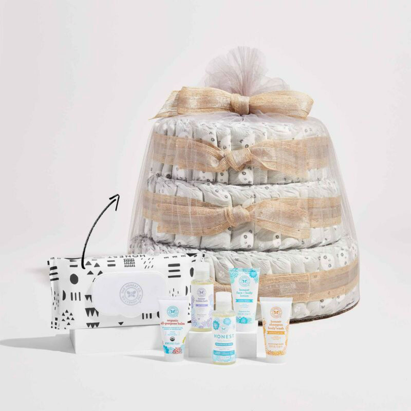 A pack of wipes, a tube each of All-Purpose Lip Balm, Bubble Bath, Baby Laundry Detergent, Face + Body Lotion, and Shampoo + Body Wash lined up in front of the Honest Diaper Cake.