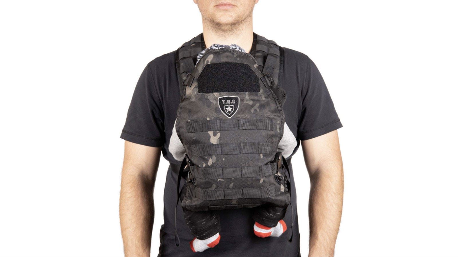 A man wearing the TBG Tactical Baby Carrier on his front, and a baby's socked feet dangling below it.