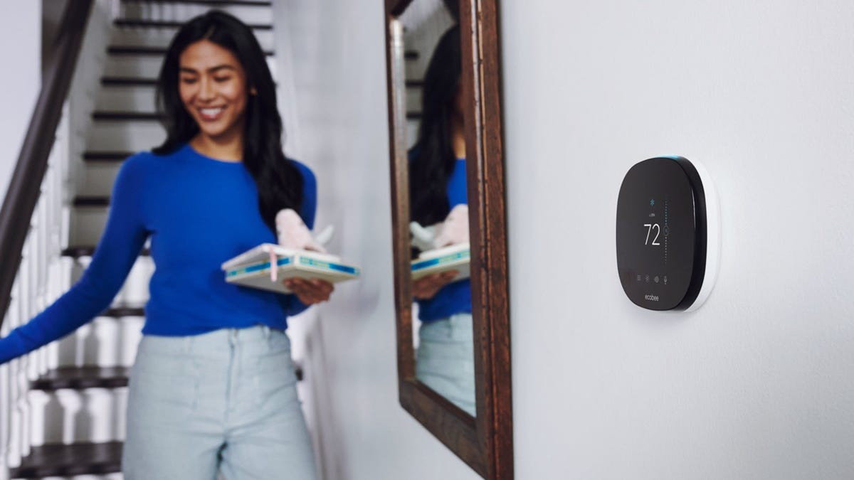A young woman walking down a set of stairs next to an Ecobee thermostat