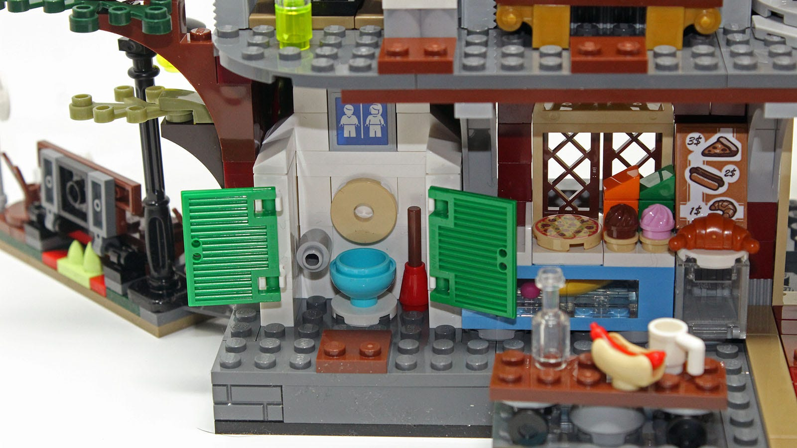 A tiny LEGO bathroom, including a plunger and toilet paper.