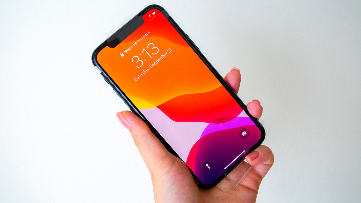 A hand holding up the iPhone 11.