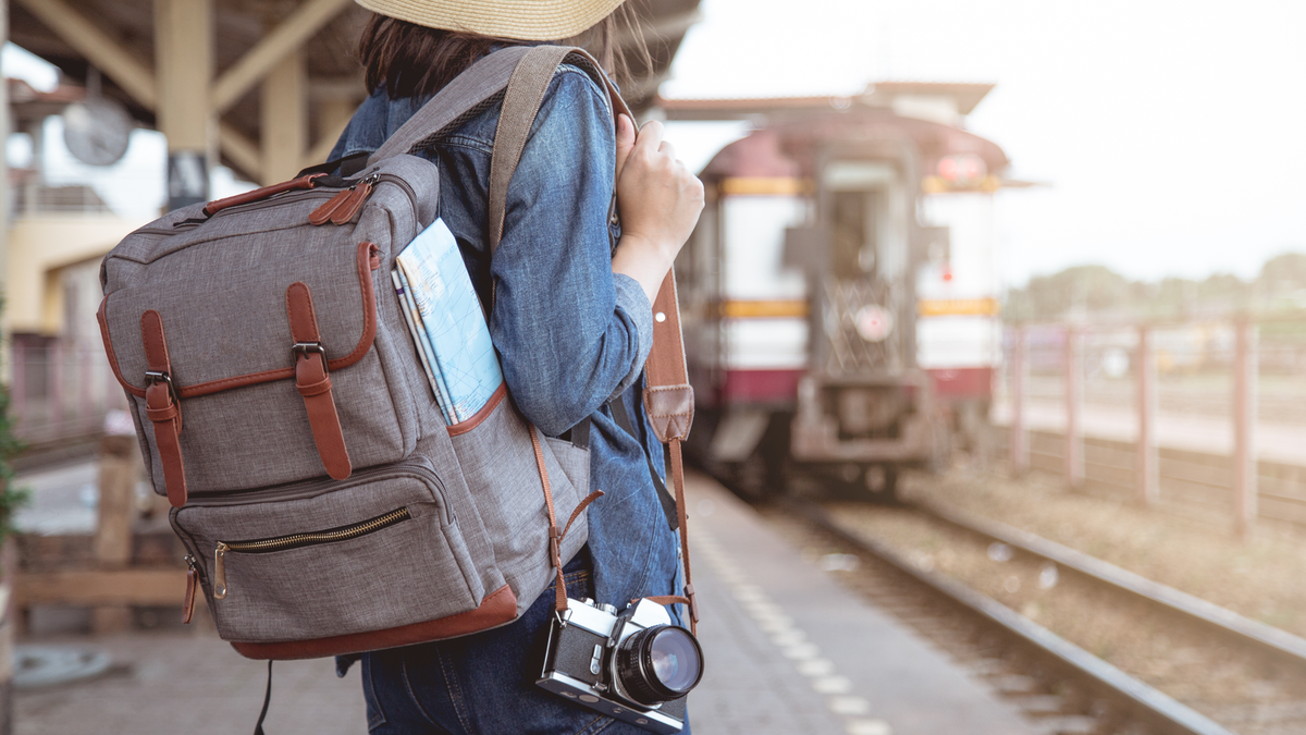 A woman with a day bag and camera slung over her shoulder waiting as a train pulls into the station.