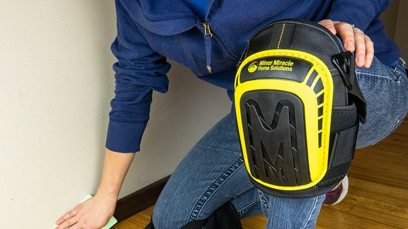 A person on one knee, wearing the yellow and black Minor Miracle Home Solutions Kneepads.