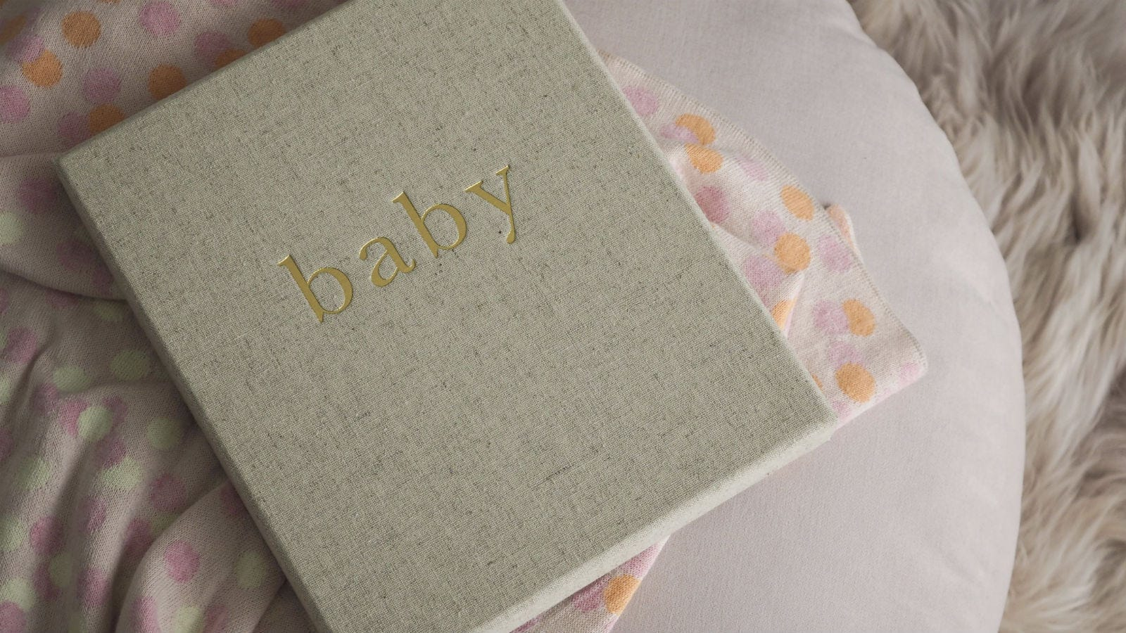 """The """"Baby"""" First Year of You Journal lying on top of a baby blanket."""