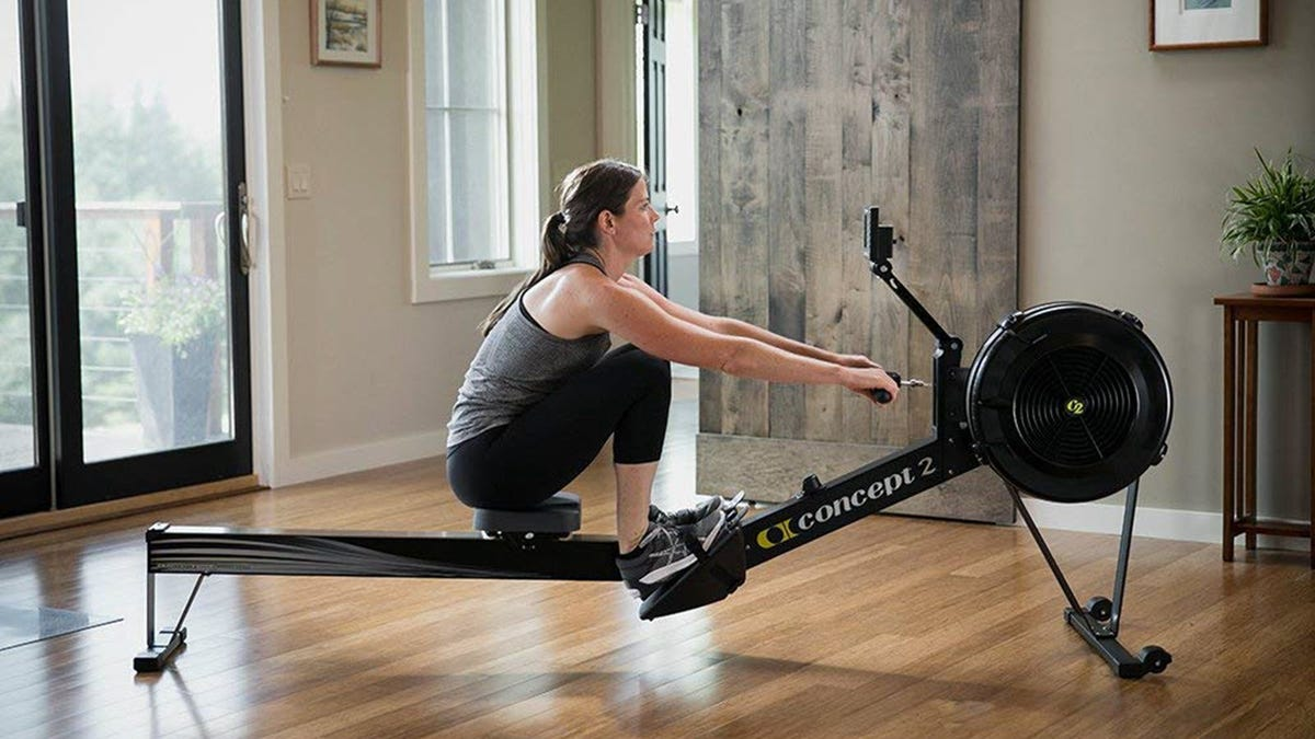 A woman using a Concept2 rowing machine in a living room.