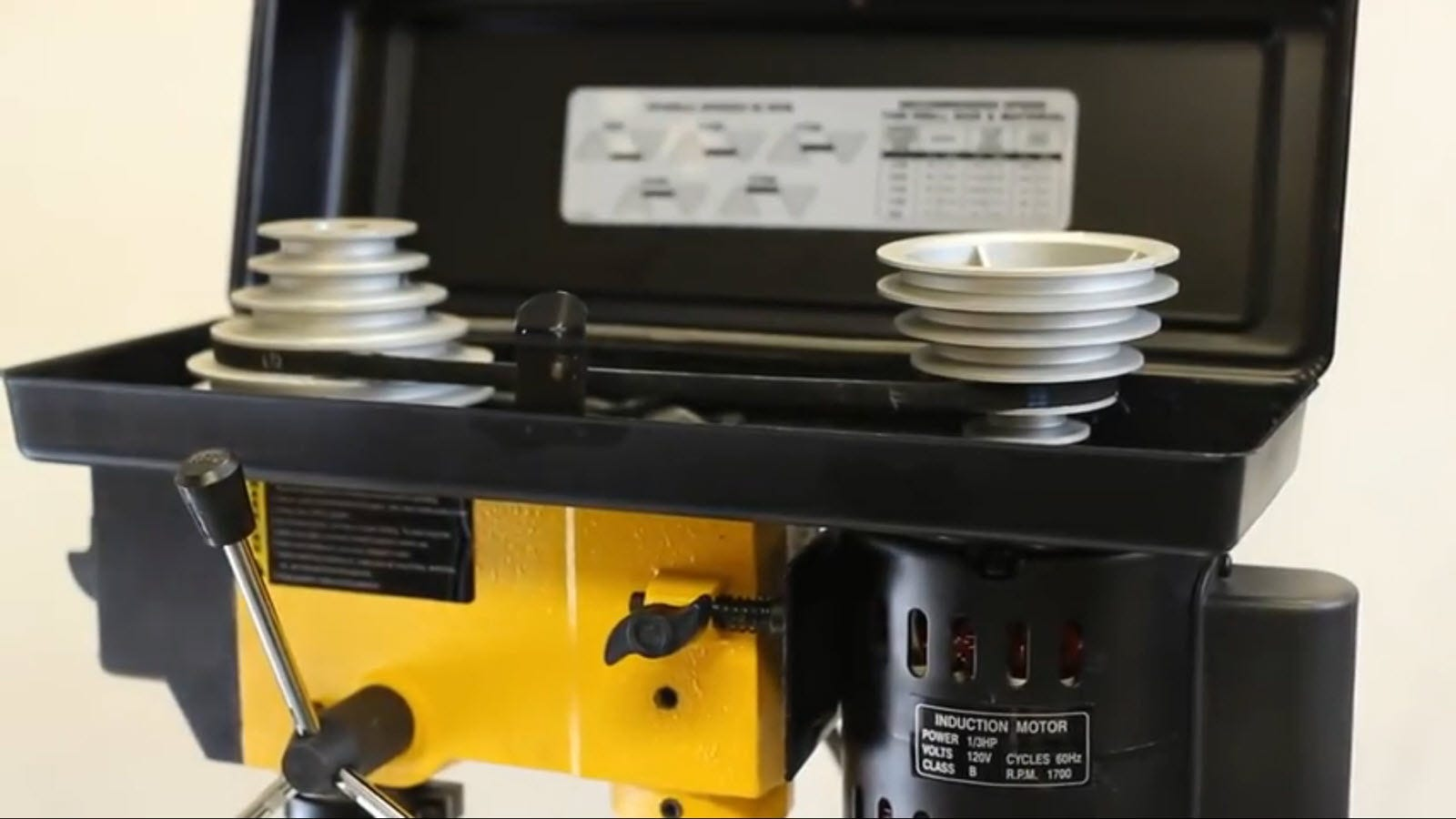 A pulley and band system in the top of a drill press.