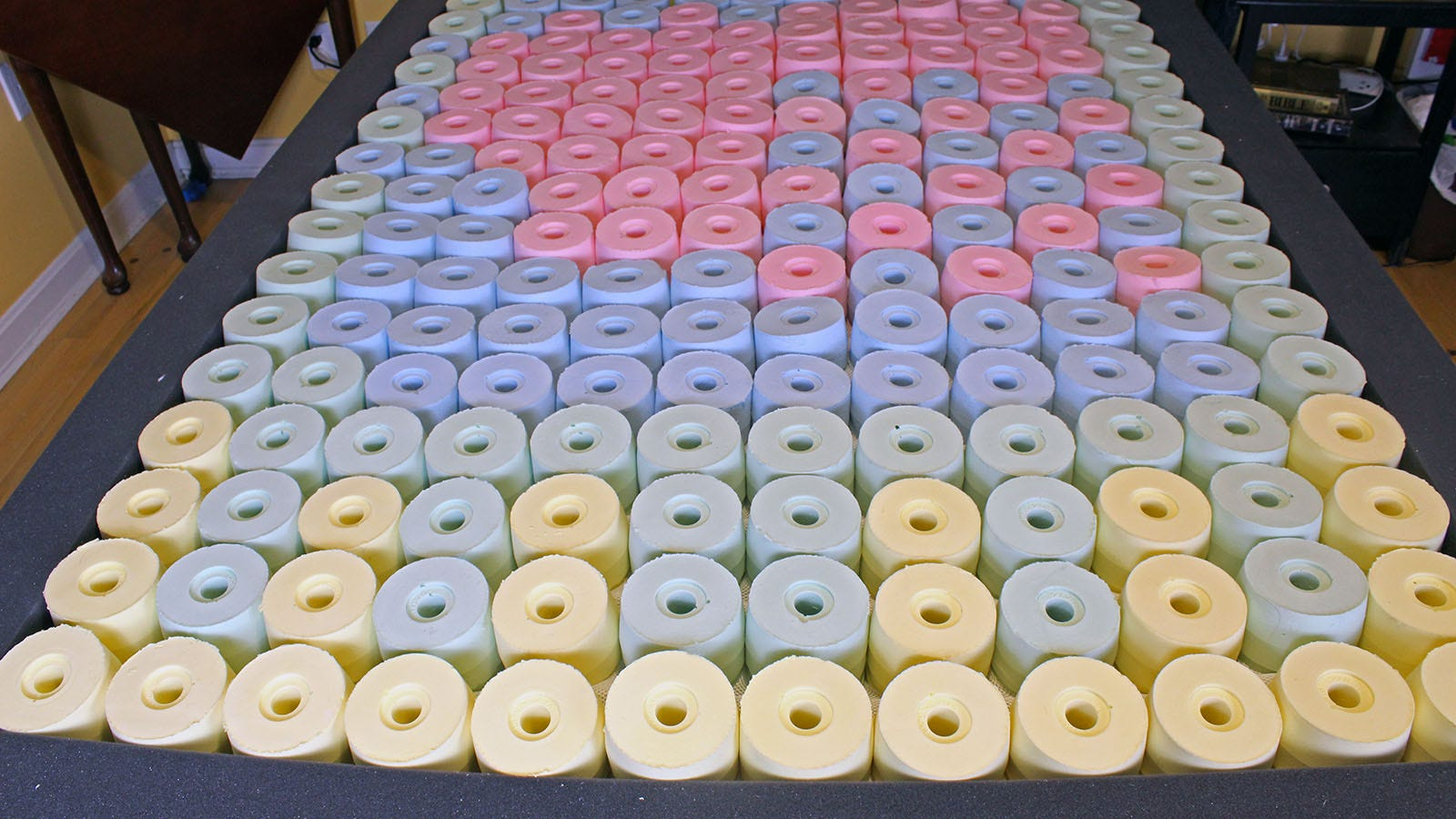 A bed full of multi-colored foam springs surrounded by a dark black border.