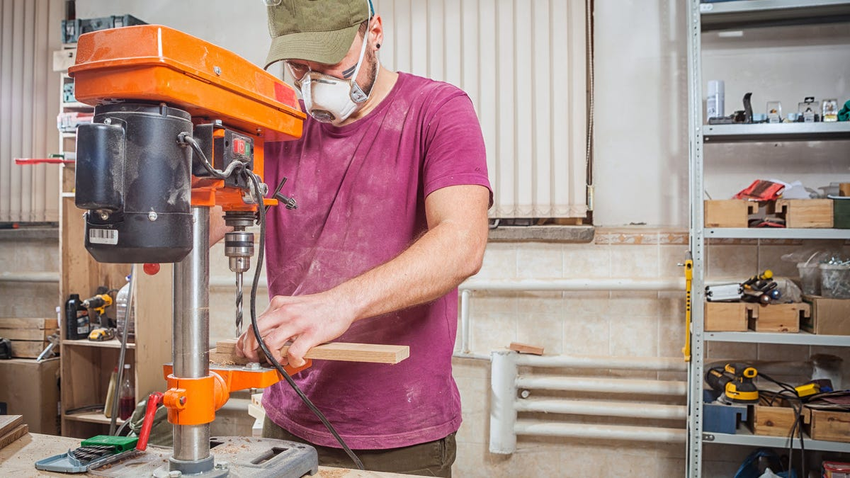 A man wearing a dust mask, using a drill press to drill holes into a wood board.