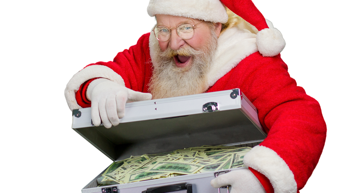 Santa Claus opening a steel briefcase full of loose cash.