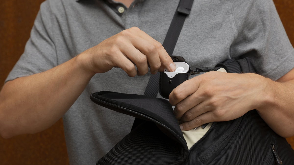 A man placing his Airpods into a TwelveSouth carrying case.