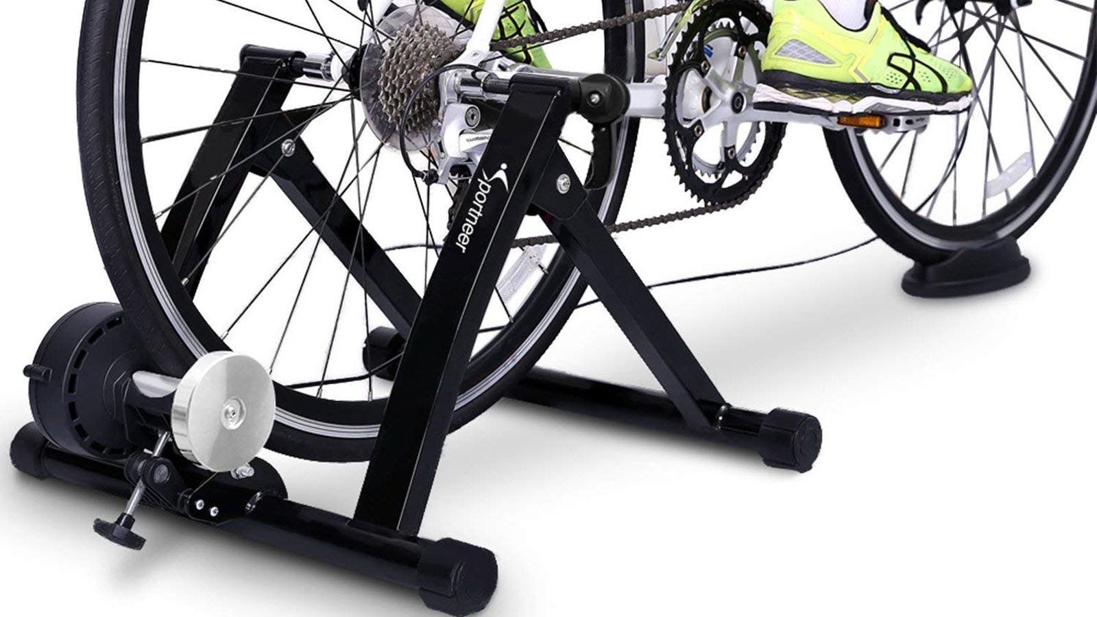 The Sportneer Bike Trainer Stand with a bike attached to it and a person's feet on the pedals.