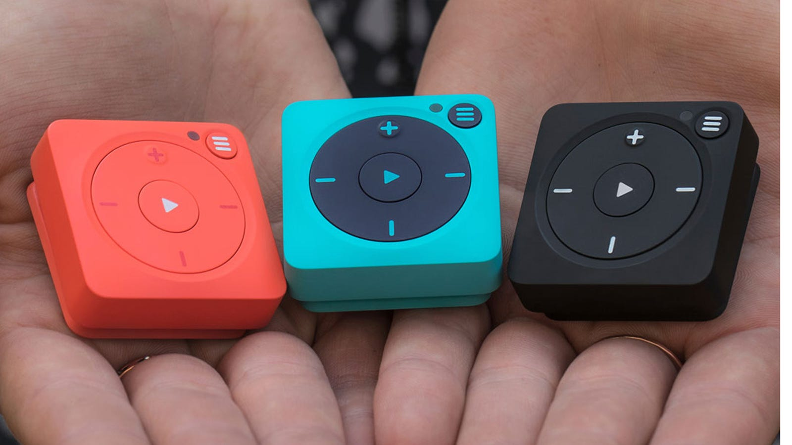 Someone's hands cupped and holding three Mighty Vibe players in red, blue, and black.