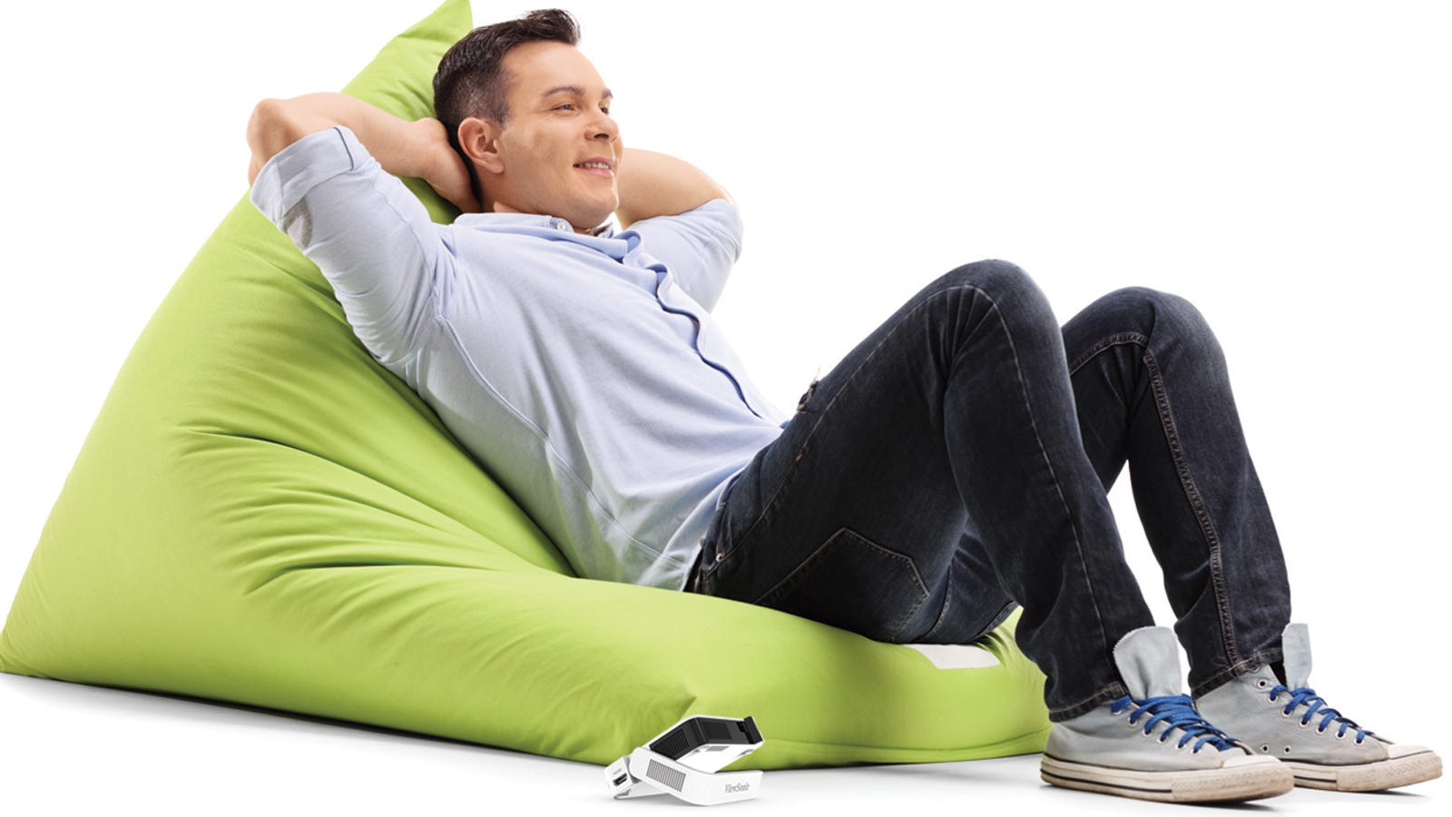Man lying on pillow ith tiny projector next to hiom on floor