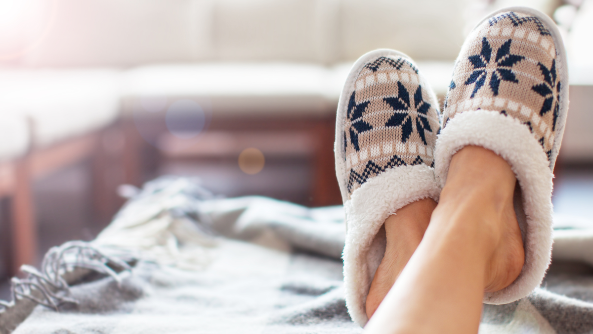 A woman's feet in slippers propped up.