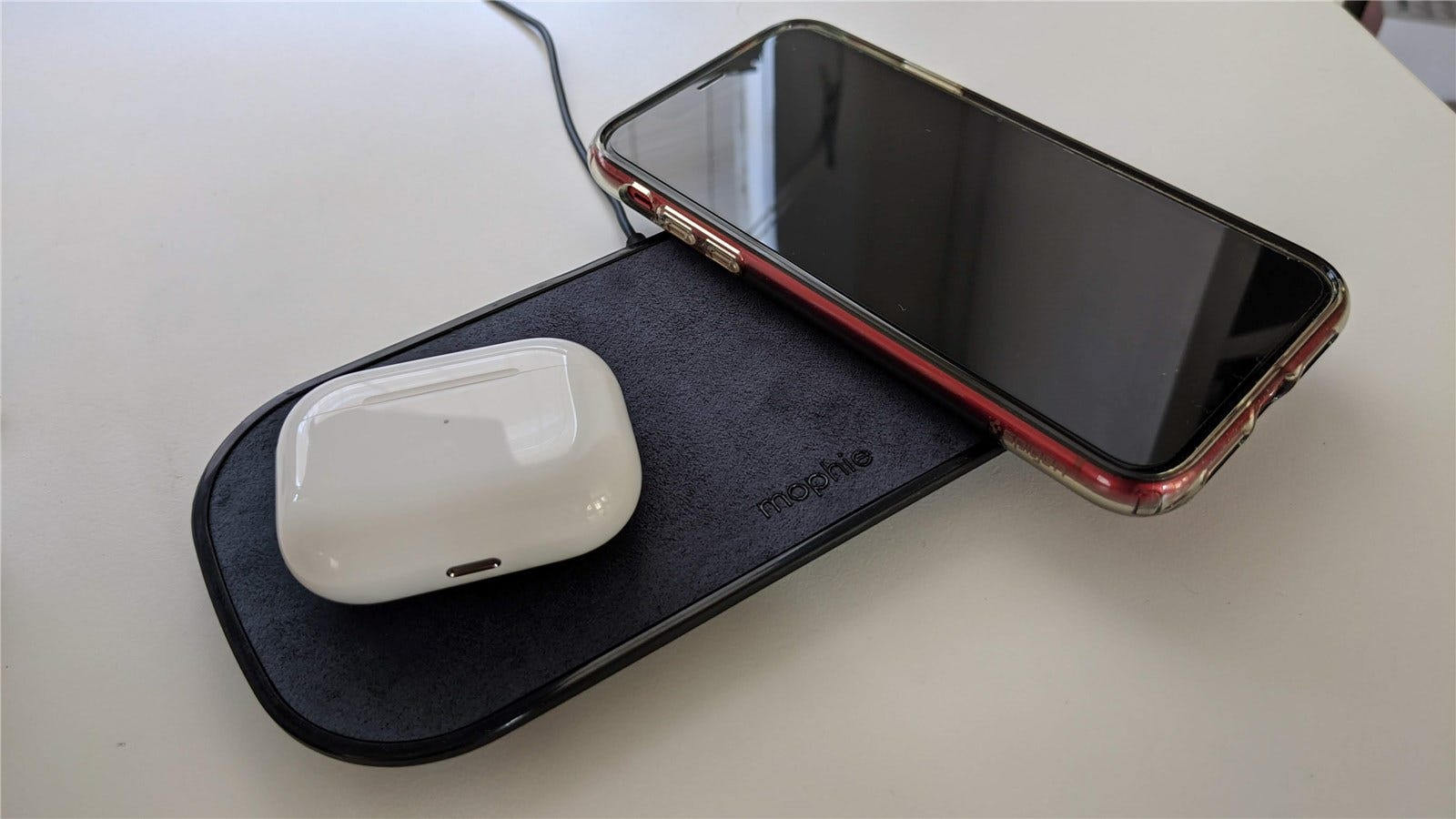 The Mophie Dual Wireless Charging Pad with AirPods and an iPhone XR on it