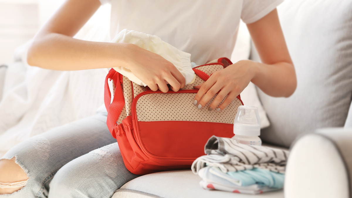 A woman packing a small diaper bag with baby stuff