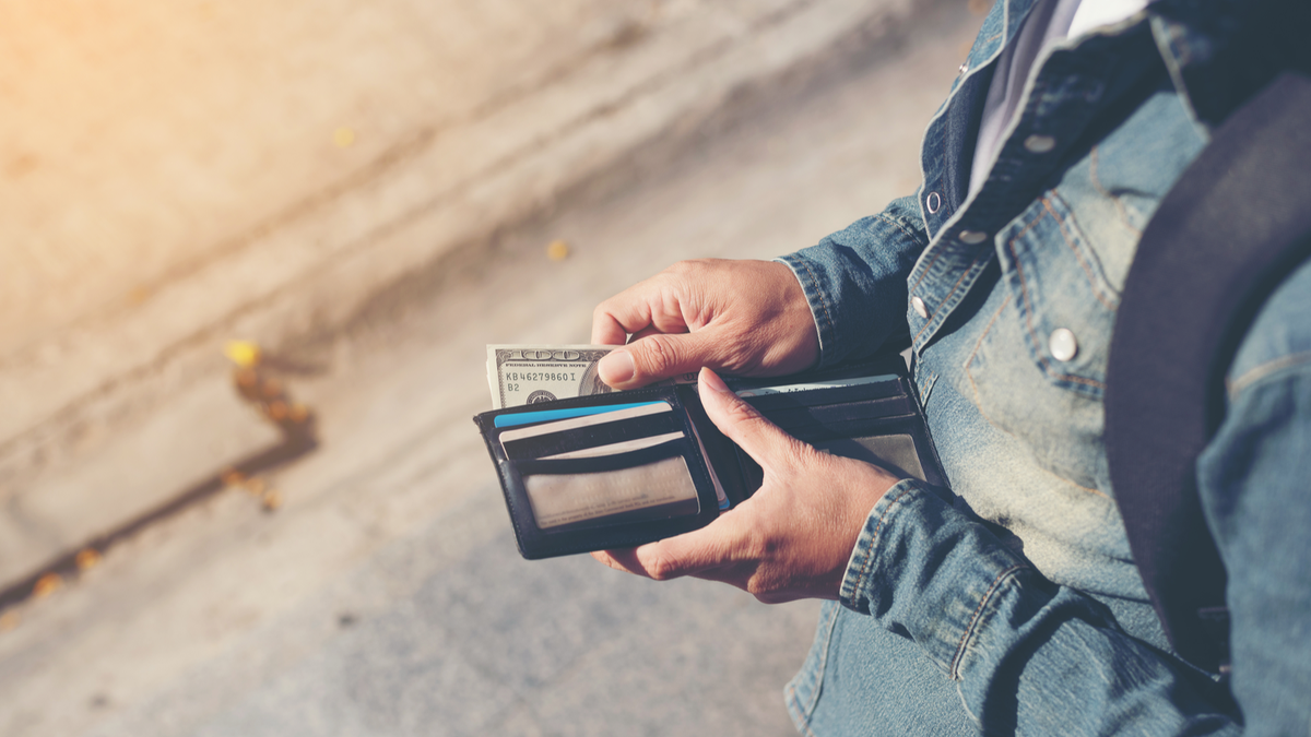 A man pulling cash from a wallet
