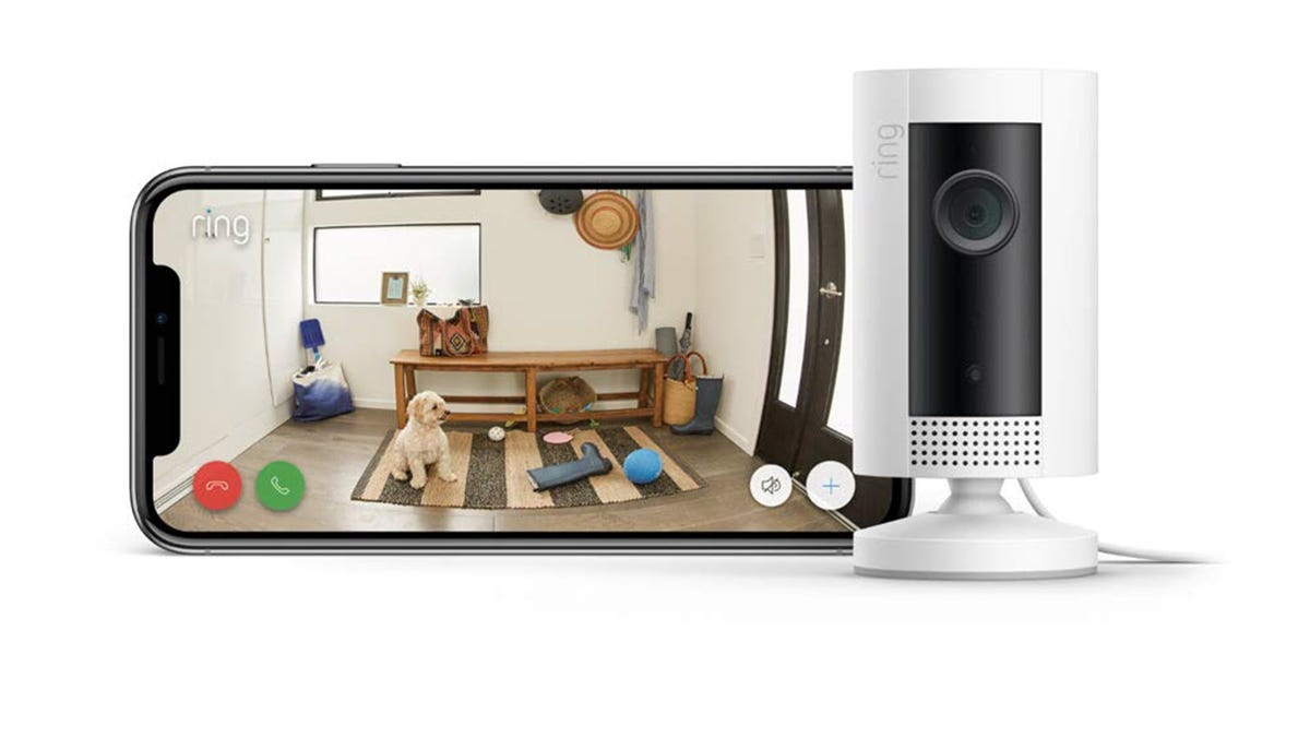 A Ring Indoor Camera next to a phone showing a live feed from the camera.