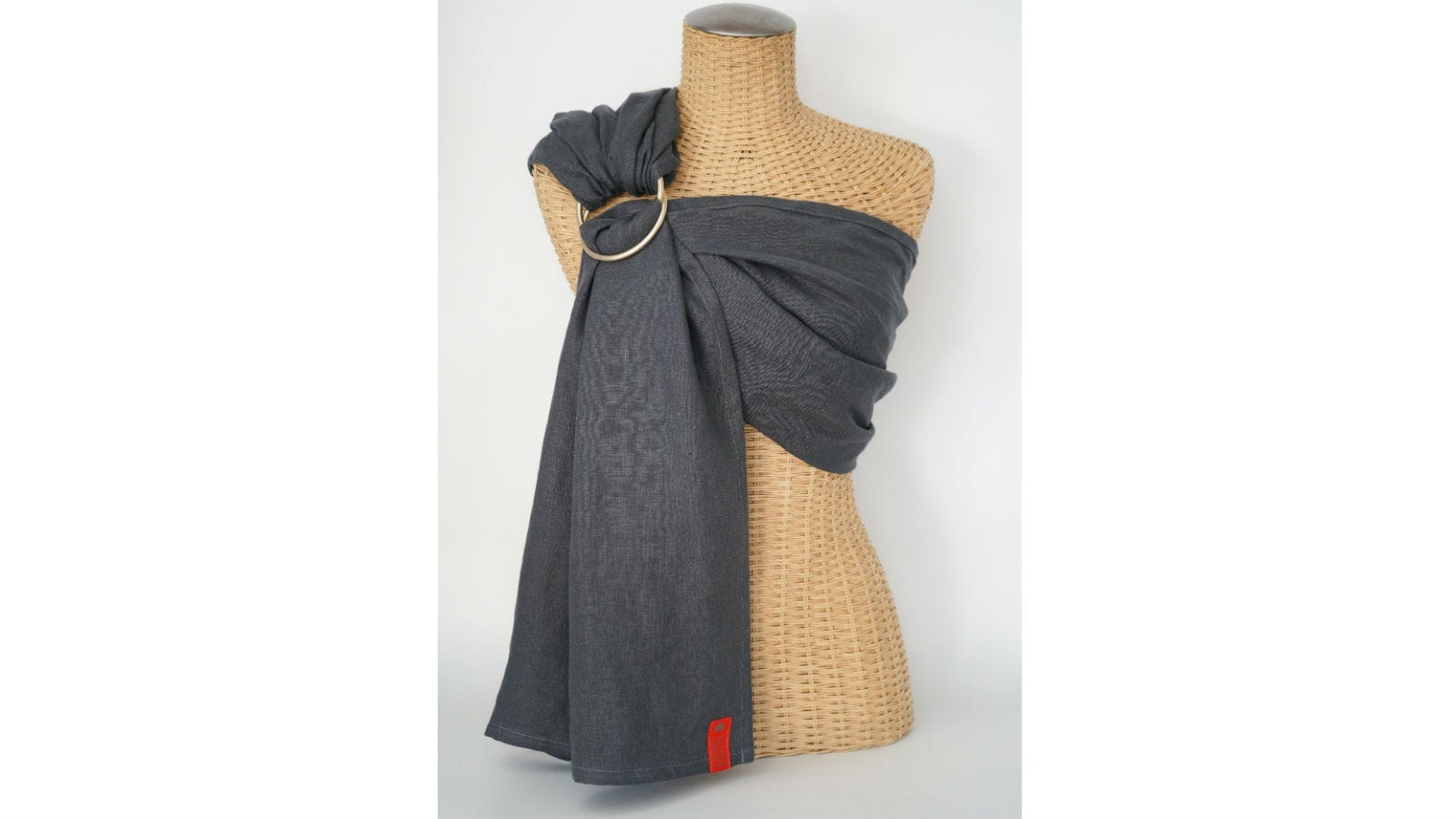 The Sakura Basics Linen Ring Sling on a headless torso wicker mannequin.