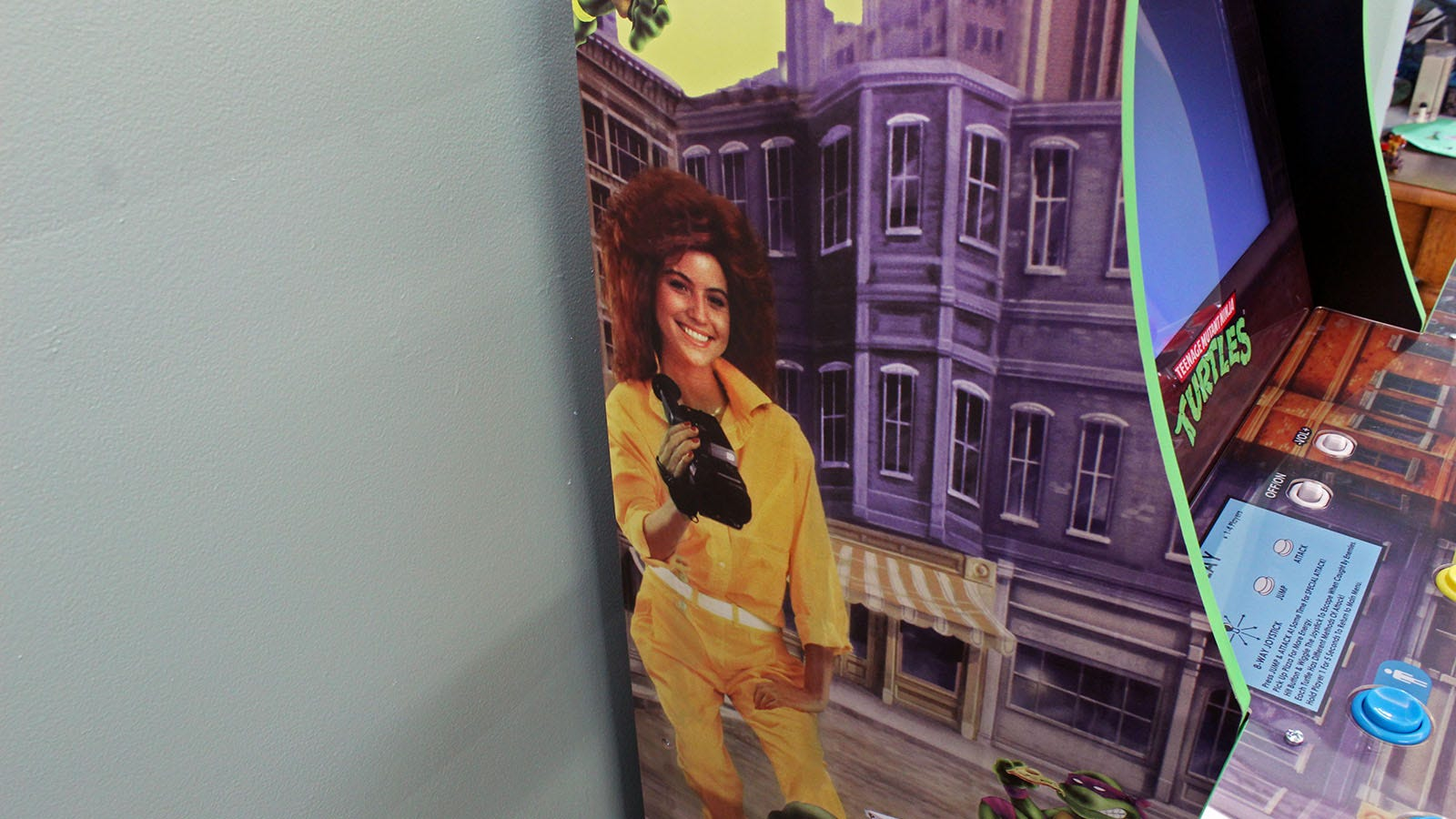 """A woman in a yellow jumpsuit with teased red hair holding an old camcorder on the side of the Arcade1Up """"Teenage Mutant Ninja Turtles"""" arcade."""