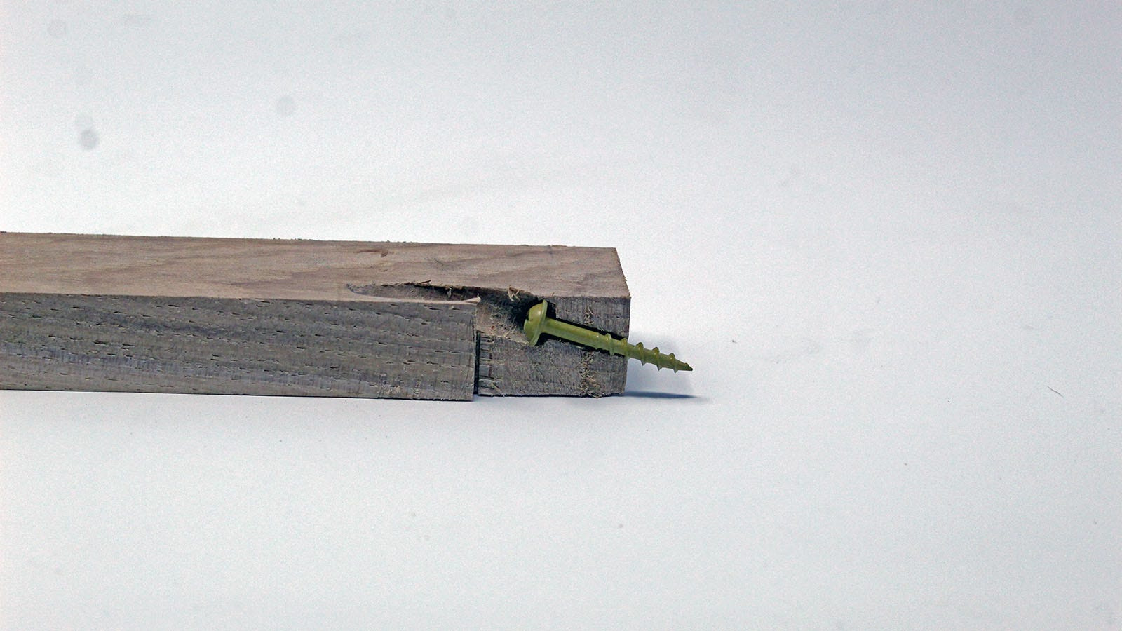 A wood board with the edge cut off, revealing the interior of a pocket hole.