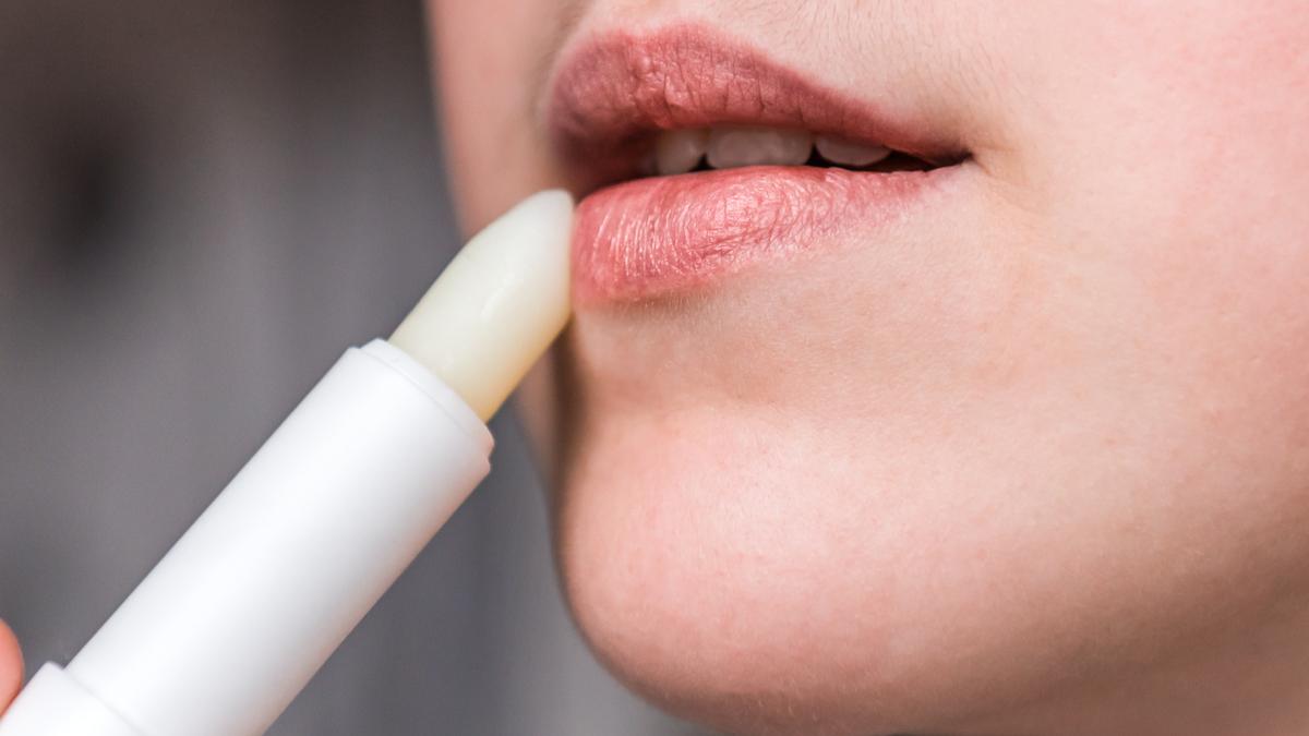 A girl applying lip balm