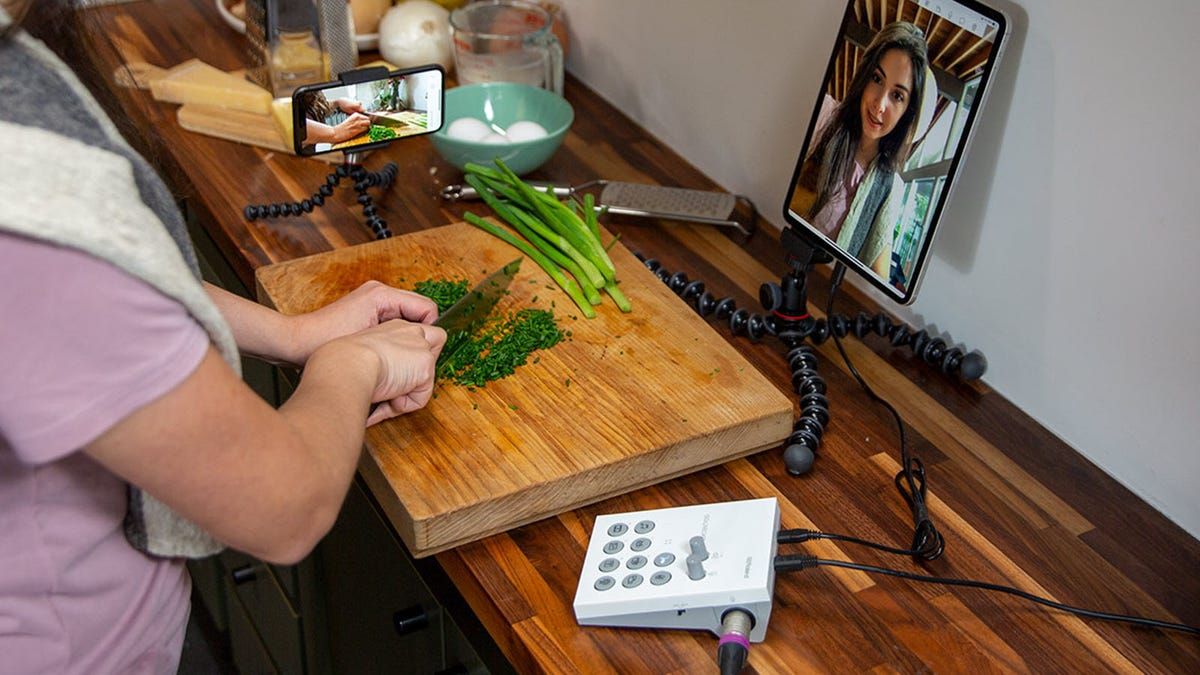 A woman, chopping vegetables while live streaming with the Roland Go:Livecast