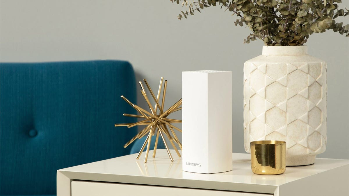 A Linksys Velop router on a cabinet next to a couch.