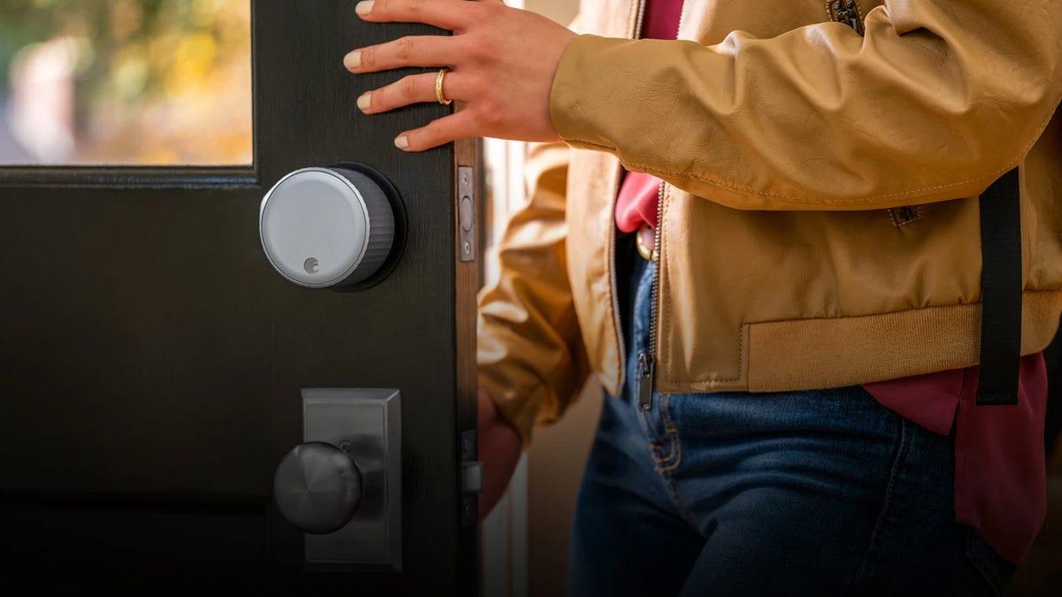 An August Wifi Smart Smart Lock on a brown door, with a man opening the door.