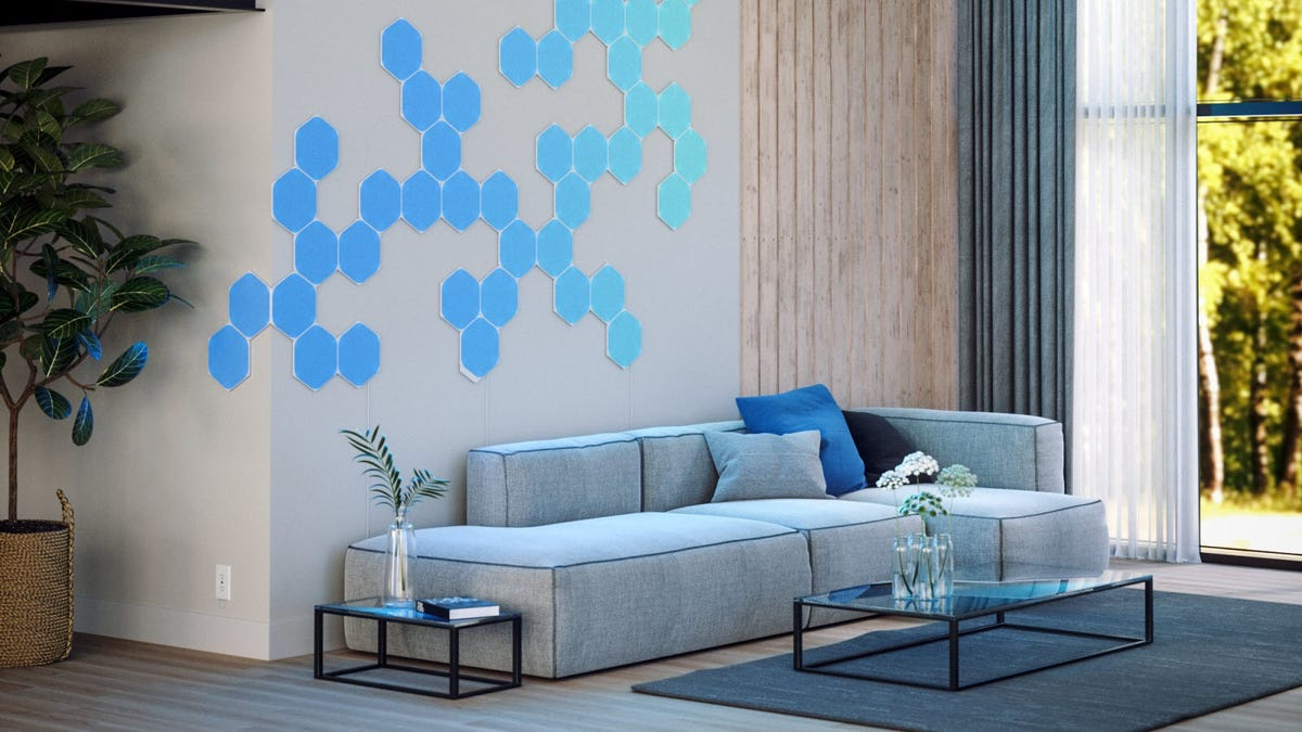 A modular couch in a modern living room, lit by 40 blue hexagonal shaped LED panels.