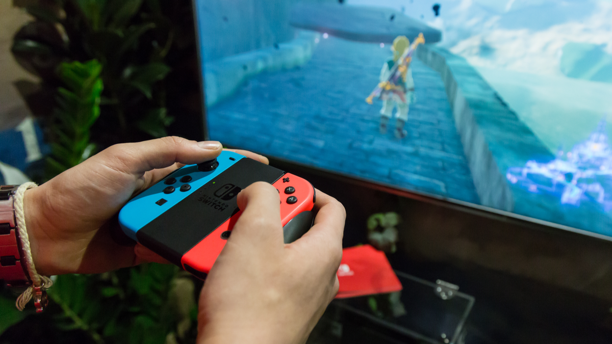 """A man's hands holding Joy-Cons and playing """"Breath of the Wild"""" on a TV."""