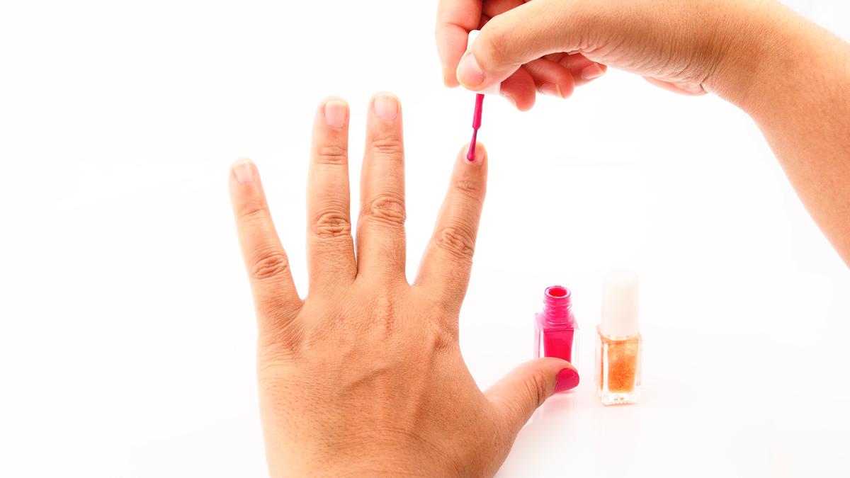 A right hand painting a left-hand index finger with bright pink nail polish.