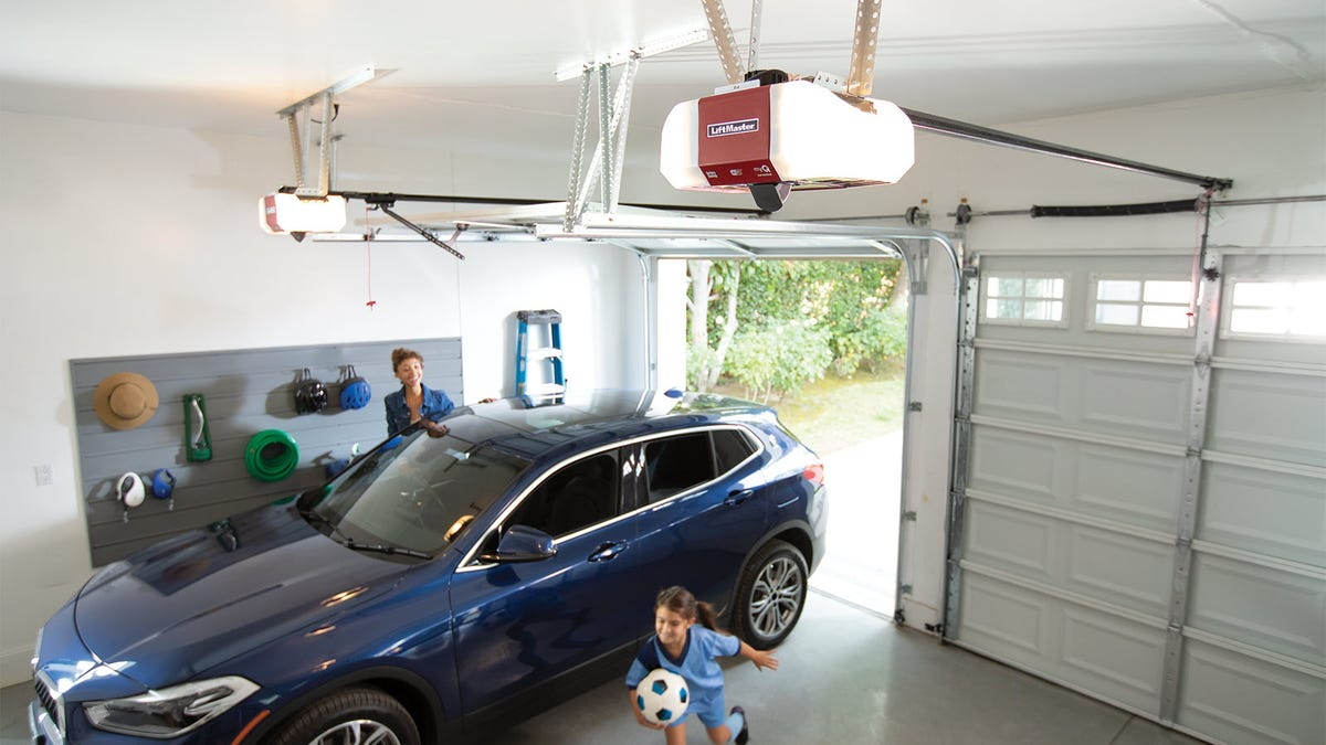 The LiftMaster WI-FI Garage Door Opener with Integrated Camera hanging in a garage above a girl with soccerball.