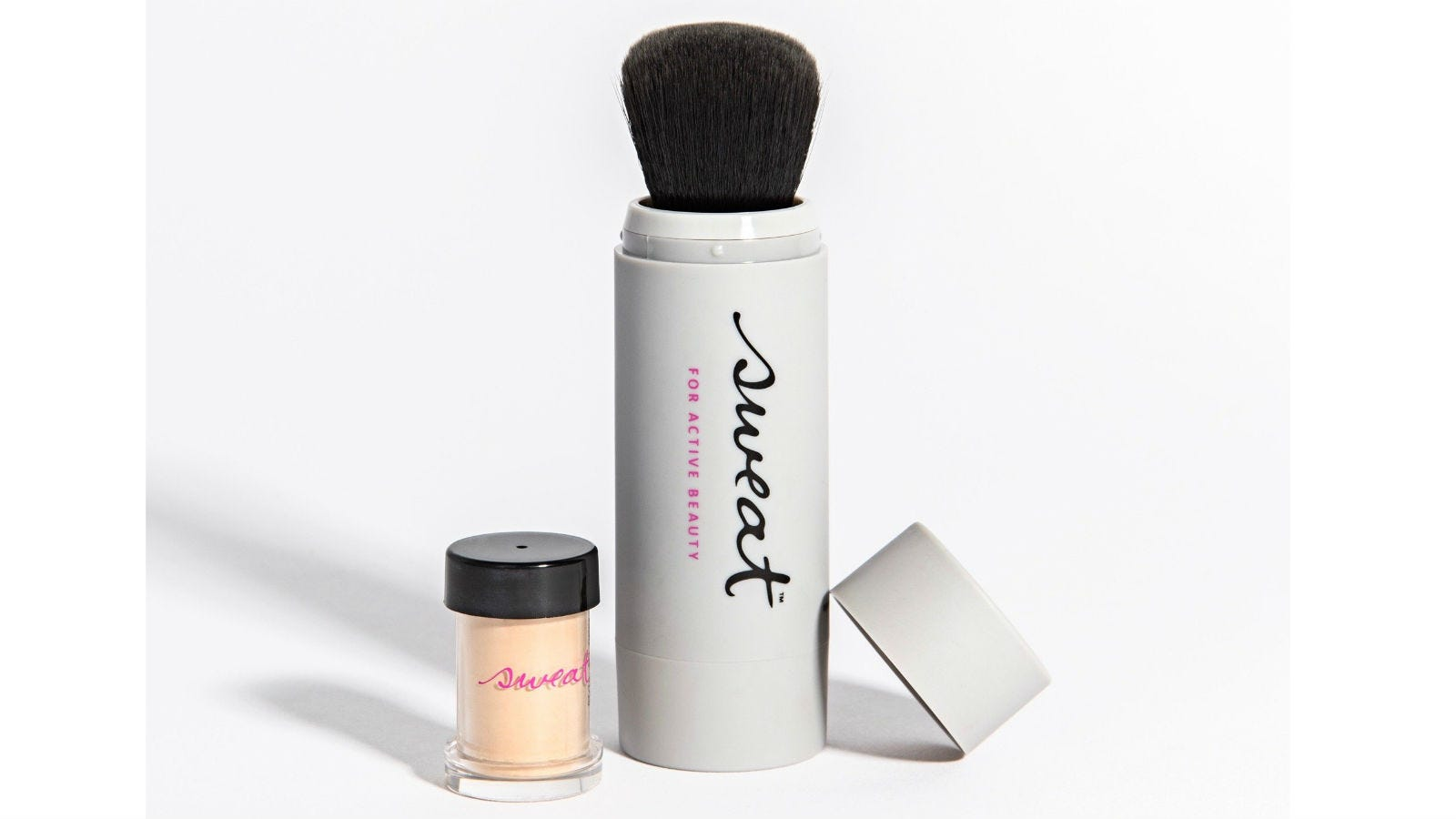 The Sweat Cosmetics Foundation Twist Brush sitting next to its cap and a small jar of foundation.