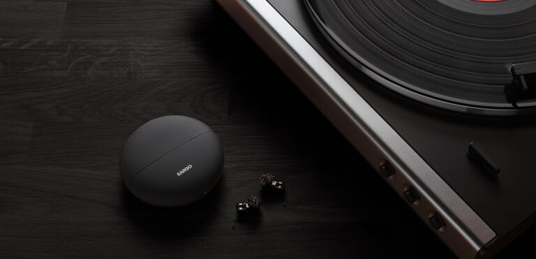 Eargo Neo Hifi with charging case, next to a record player.