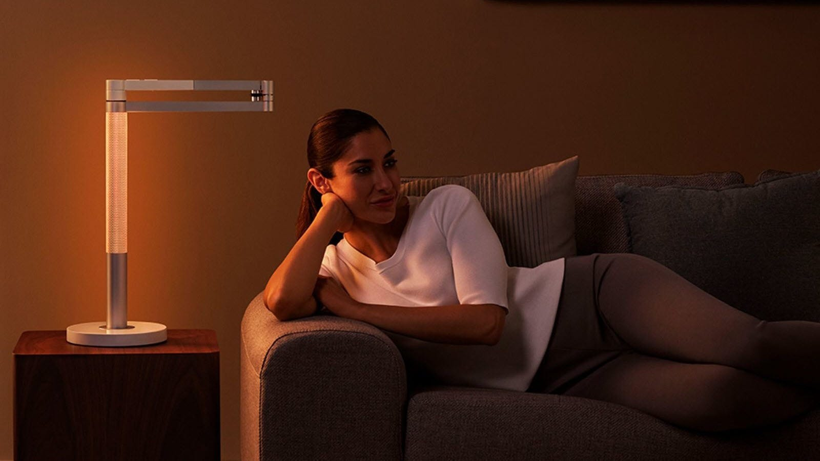 A woman laying on a couch next to the Dyson Lightcycle Morph with the head shining light through the stem.