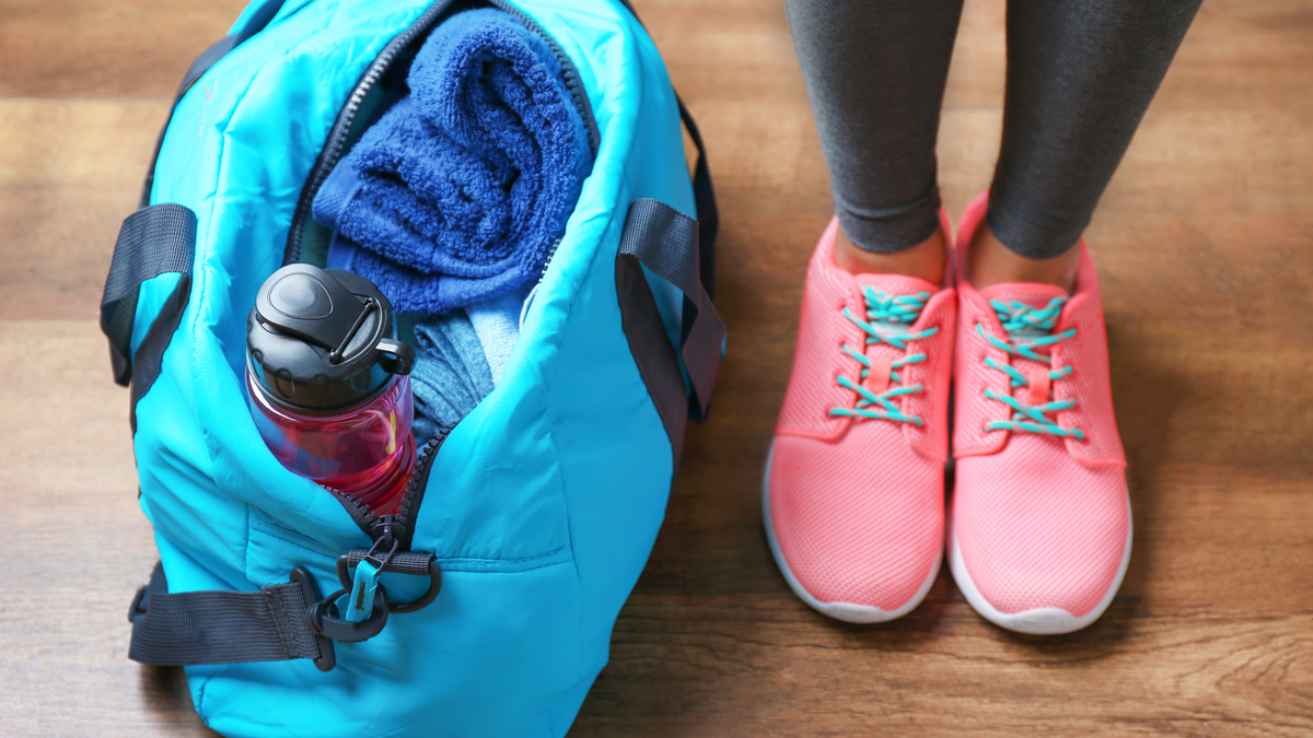 A woman's feet in sneakers standing next to a gym bag with a towel and water bottle inside.