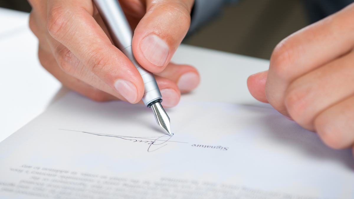 A man's hand signing a document with a fountain pen.